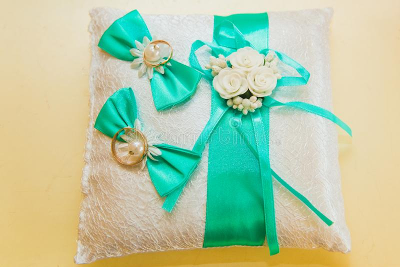 Wedding rings are on a white pillow and sadely the bride`s bouquet royalty free stock images
