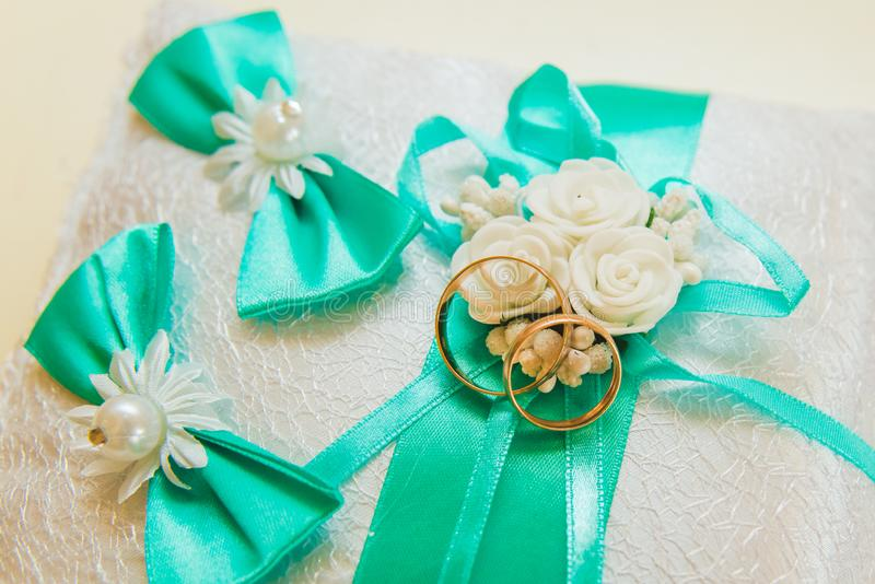 Wedding rings are on a white pillow and sadely the bride`s bouquet stock photo