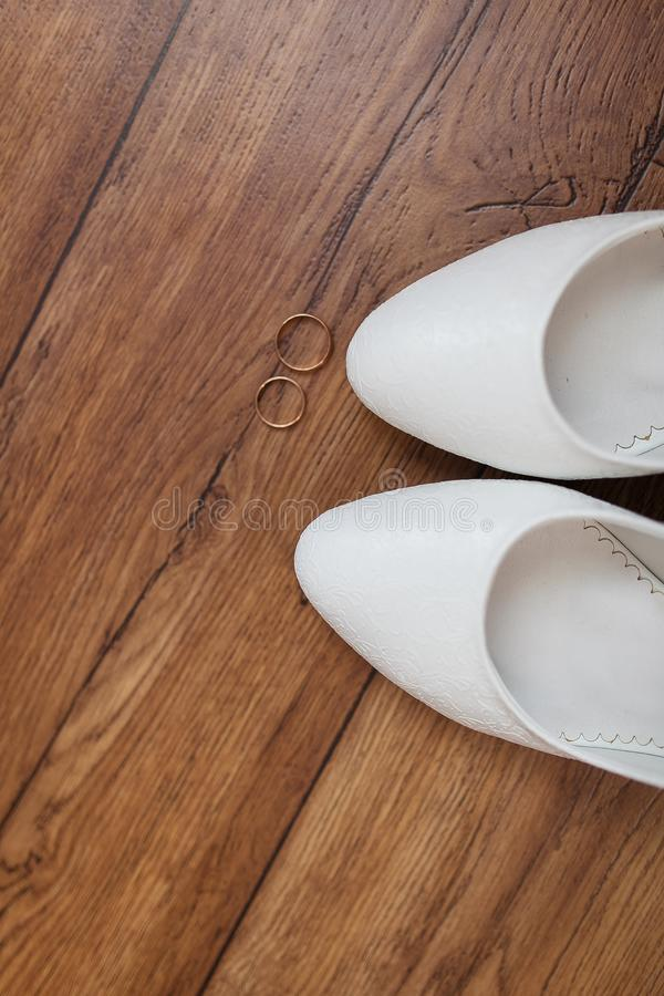 Wedding rings and white shoes on a wooden background. Wedding accessories for the beautiful bride. Wedding rings and white shoes on a wooden background royalty free stock photos