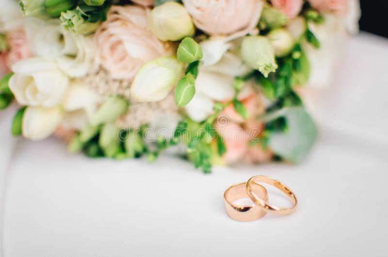 Wedding rings on white surface against flowers royalty free stock photos