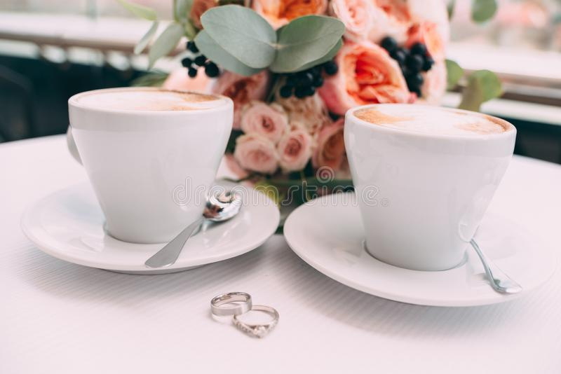 Wedding rings on a white table on the background of a wedding bouquet and two cups of coffee stock photography