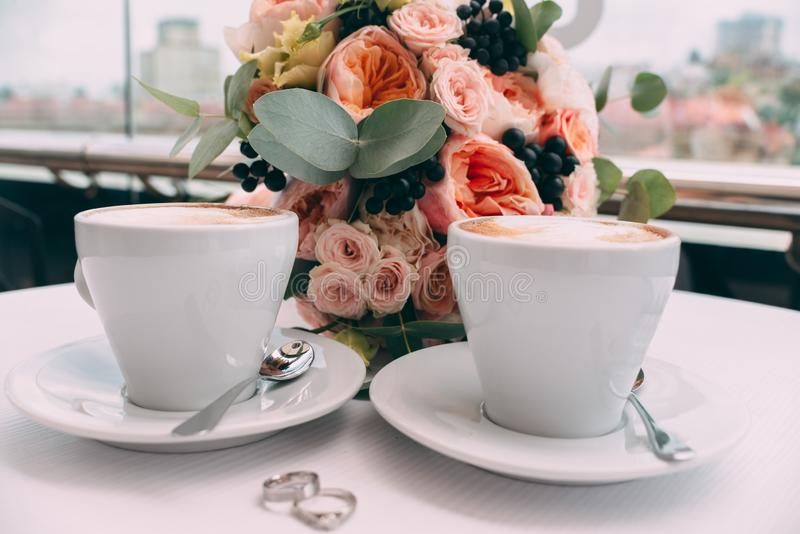 Wedding rings on a white table on the background of a wedding bouquet and two cups of coffee royalty free stock image