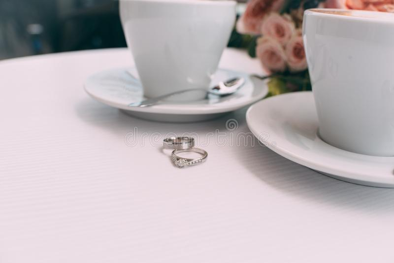 Wedding rings on a white table on the background of a wedding bouquet and two cups of coffee stock photo