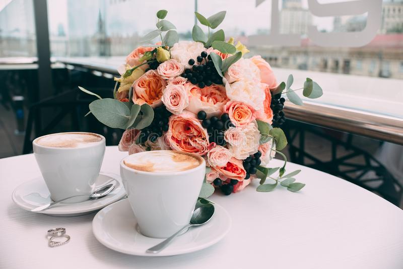 Wedding rings on a white table on the background of a wedding bouquet and two cups of coffee royalty free stock photography