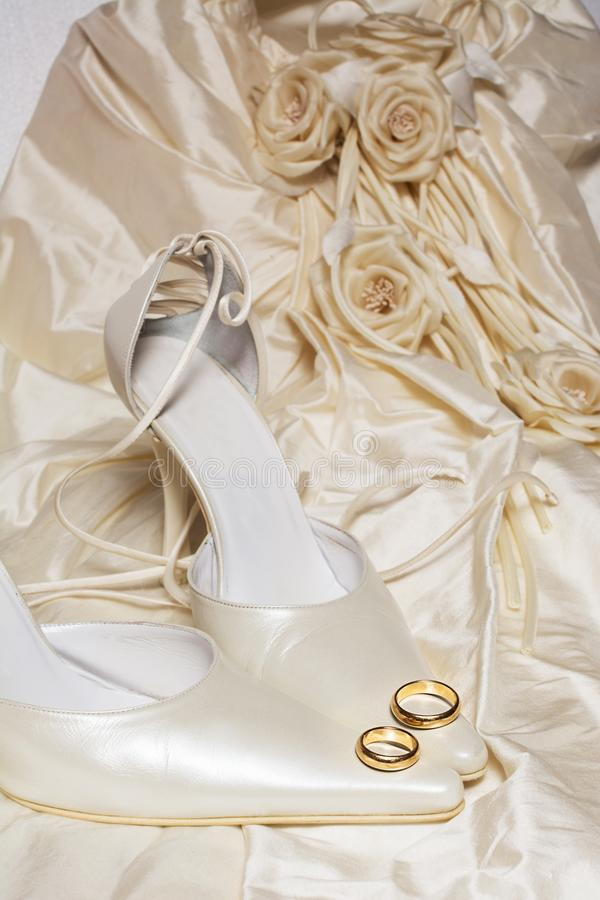 Wedding rings and women`s shoes with a dress on the background. Two wedding rings and women`s shoes with a dress on the background royalty free stock photography