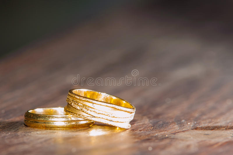 Wedding rings on wood texture stock images