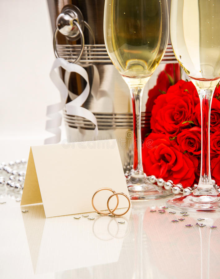 Wedding rings with writing card and champagne stock images