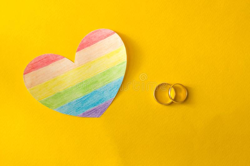Wedding rings on a yellow background and a heart in the form of a flag lgbt, same-sex marriage, homosexuality. And lesbian stock photography