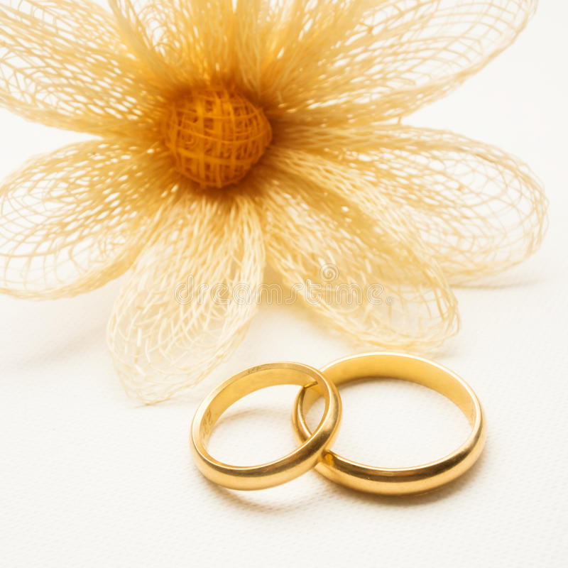Wedding rings and yellow flower royalty free stock photos