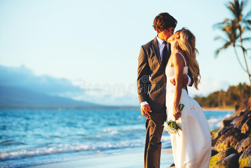 Wedding. Romantic Wedding Couple Kissing on the Beach at Sunset stock image