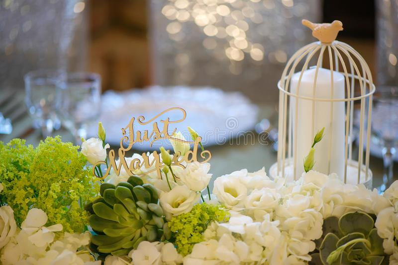 Wedding romantic decor for bride and groom dinner table with white vintage decorative bird cage holding a white candle stock image