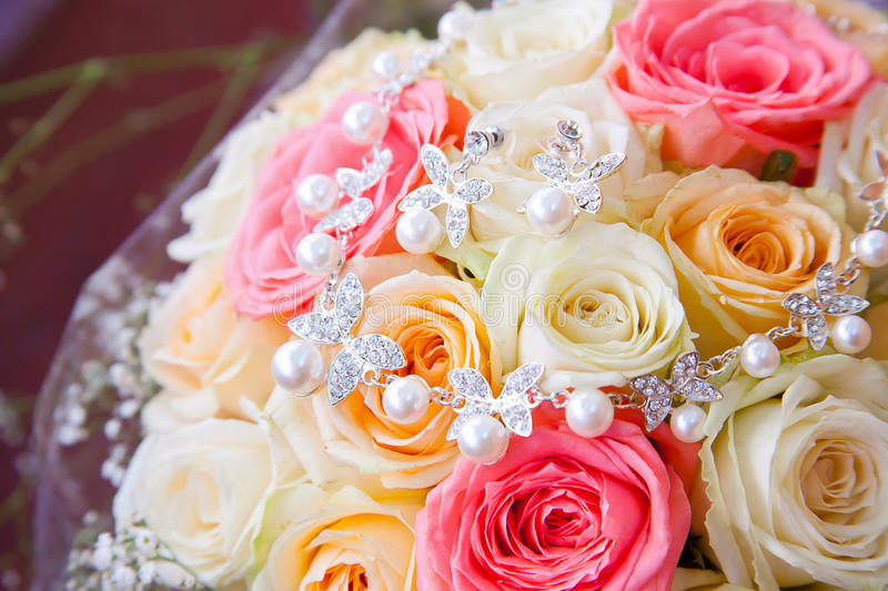 Wedding rose bouquet and silver necklace with pearls. Wedding rose flowers bouquet and silver necklace with pearls stock image