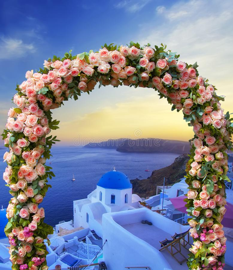 Wedding at Santorini. Beautiful arch decorated with flowers of roses with  blue church of Oia, Santorini, Greece at most romantic stock photos