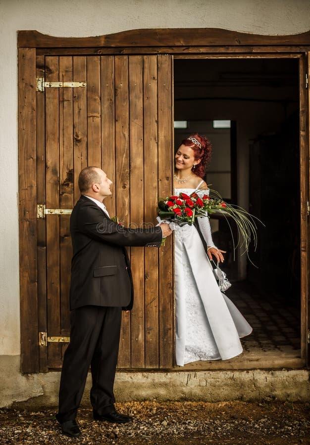 Wedding scene. Groom giving bouquet to his bride