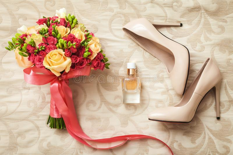 Wedding set of bridal bouquet, white shoes and perfume. Wedding set of beautiful and colorful bridal bouquet tied with ribbon, white shoes on heels, luxury royalty free stock photography