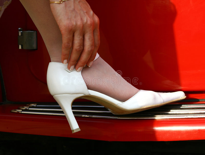 Wedding shoe. Brides shoe on the red cars stock photo