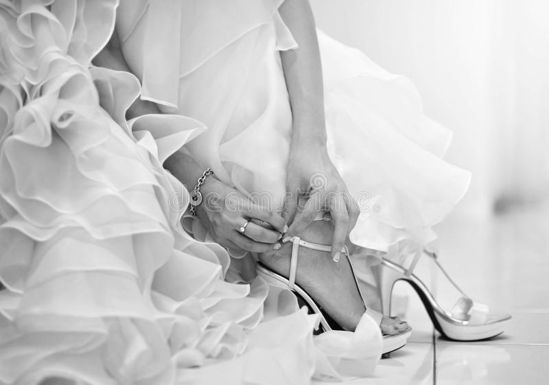 Wedding shoes. The bride is putting on her shoes for the wedding day stock photo
