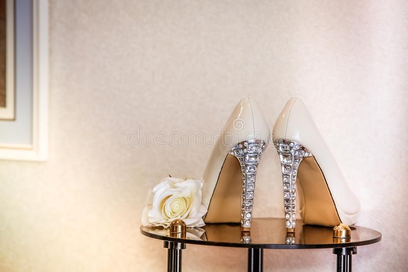 Wedding shoes beige high-heeled decorated with precious stones. Wedding shoes with high heels are on the mirror table royalty free stock images