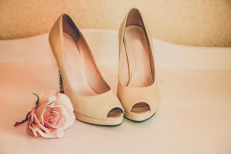 Wedding shoes beige high-heeled stand on the dresser royalty free stock photos