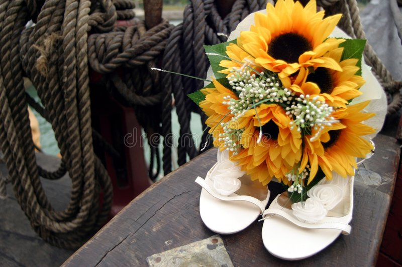Wedding shoes and bouquet. A pair of white wedding bridal shoes and a flower bouquet on an old sailing ship stock image