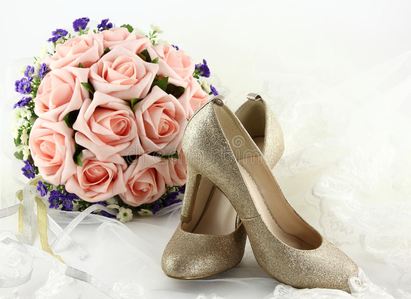 Wedding shoes and a bouquet of flowers. This graph is a pair of golden wedding shoes and a bouquet of flowers stock image