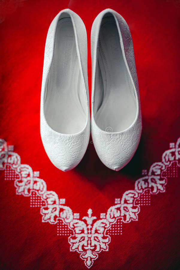 Wedding shoes. Bride. Ceremony shoes on red background royalty free stock photo