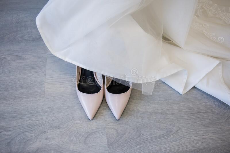Wedding shoes of the bride next to the dress. Stand next to stock photos