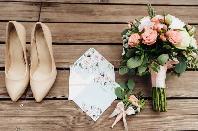 Wedding shoes of the bride together with a bouquet of natural flowers.  stock images