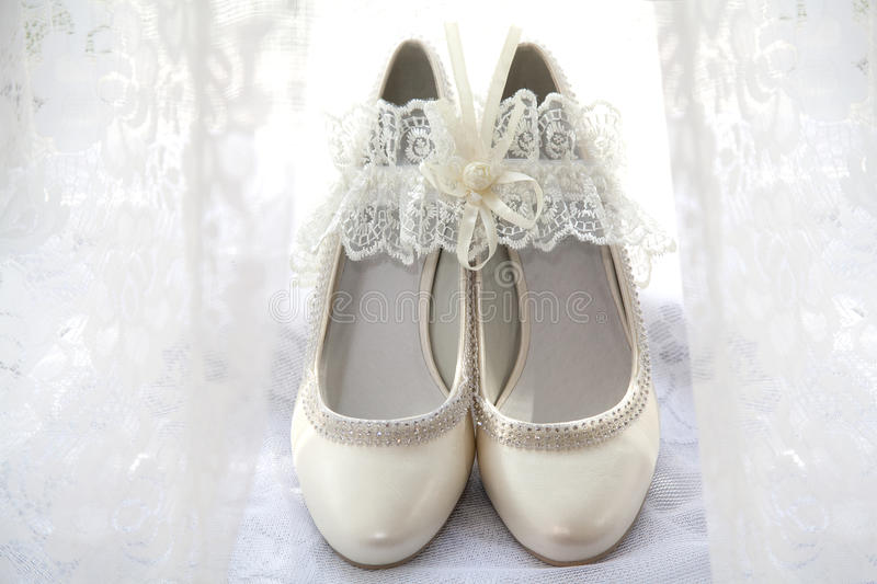 Wedding shoes. And garter. Beige stock photo
