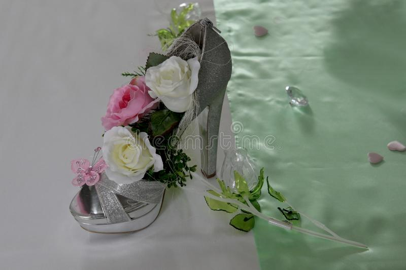Wedding shoes table decoration. Wedding shoes with high heels with roses standing on a decorated table royalty free stock images