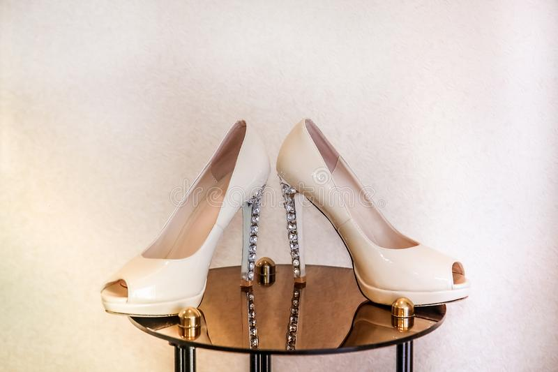 Wedding shoes with high heels stand on a mirrored table and decorated with precious stones royalty free stock image