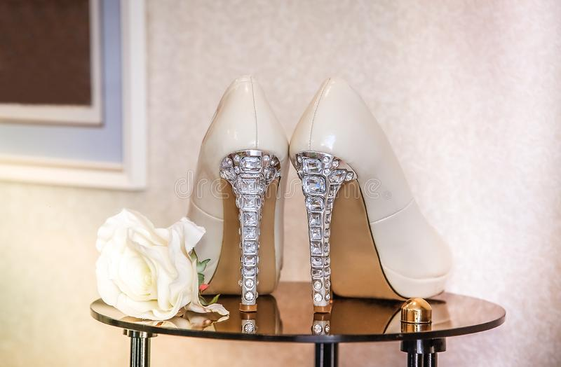 Wedding high-heeled shoes decorated with precious transparent stones. Wedding shoes with high heels stand on a mirrored table and decorated with precious stones stock images