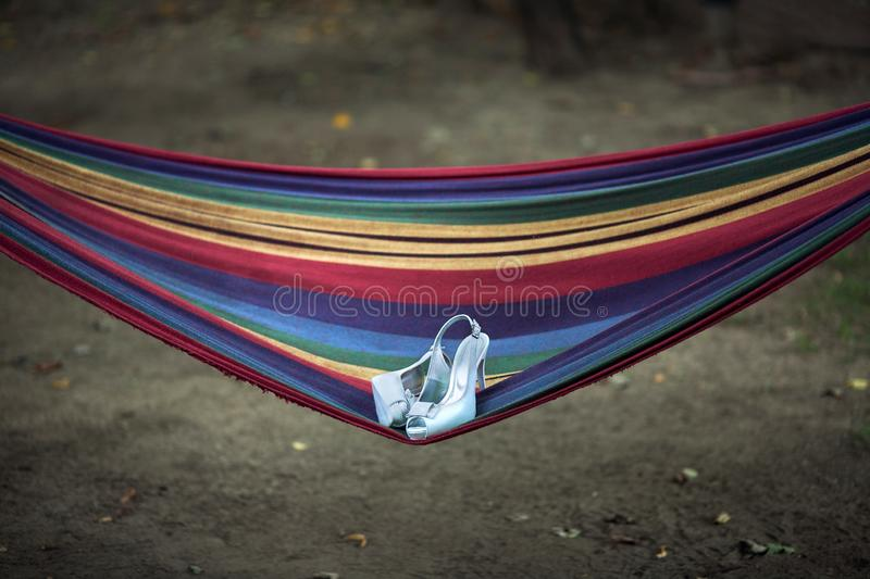 Wedding shoes lie on a hammock royalty free stock photos