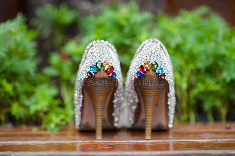 Wedding shoes. One pair of inlaid with colored stones wedding shoes background is green grass stock photography