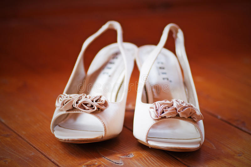 Wedding shoes. Pair of woman's wedding shoes sitting on the wooden floor royalty free stock image