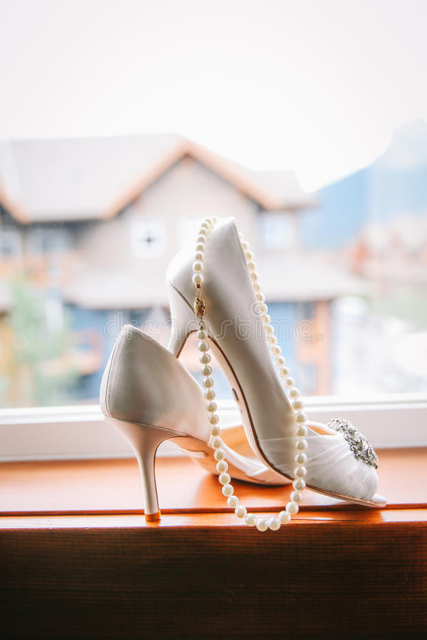 Wedding shoes and pearl necklace stock photos