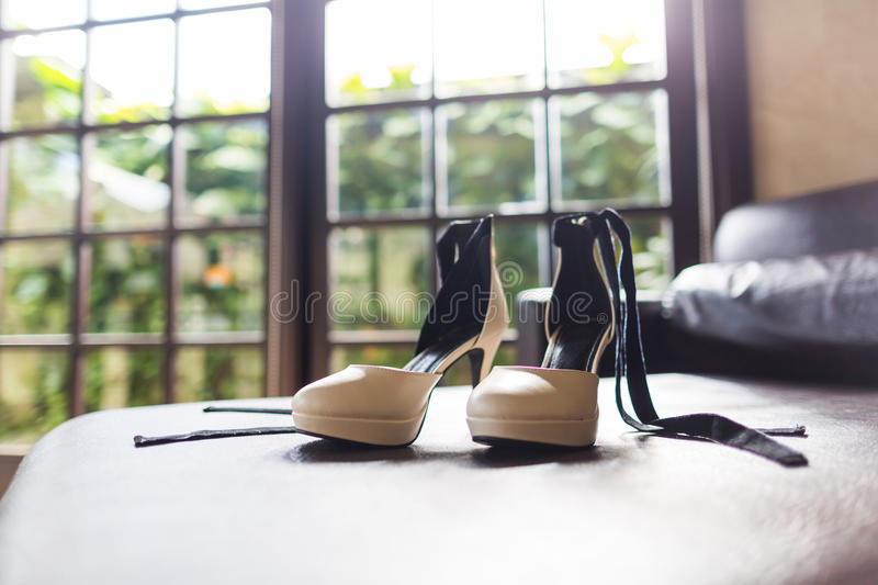 Wedding shoes. On the sofa beside the window royalty free stock photos
