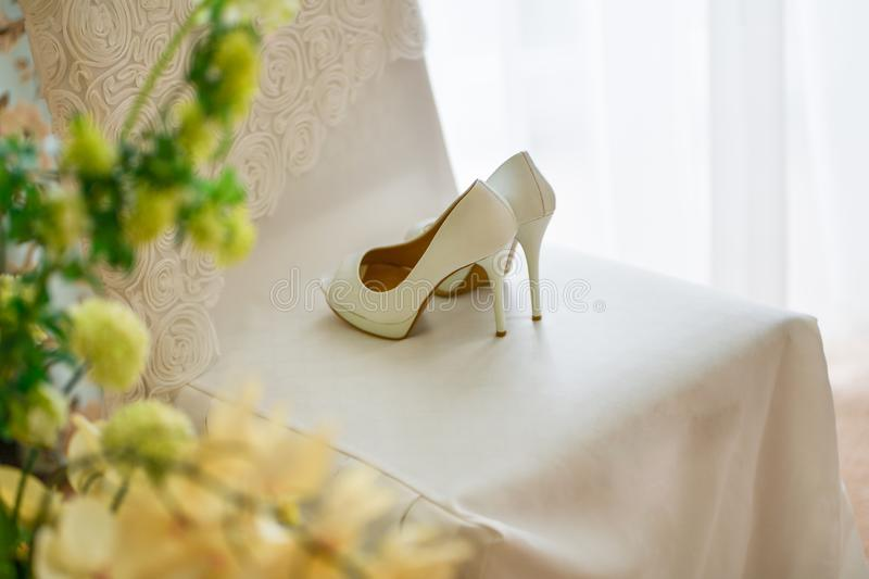 Wedding shoes stand on a white chair. Wedding shoes stand on a chair stock photos