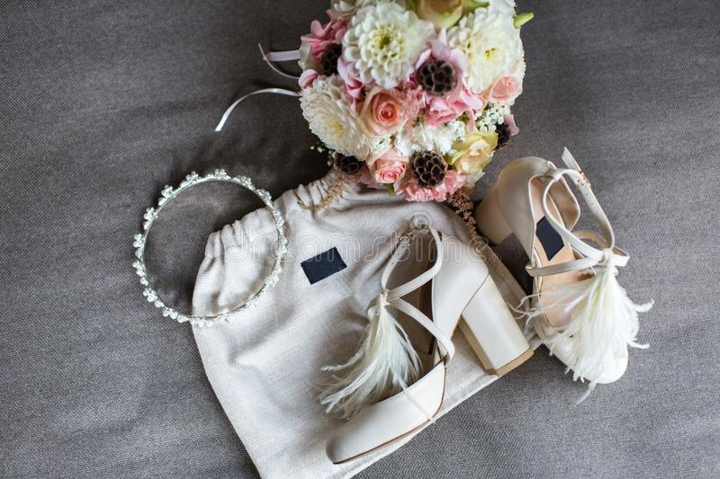 Wedding shoes, tiara and bouquet on a gray background stock image