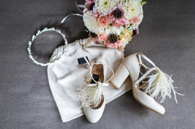 Wedding shoes, tiara and bouquet on a gray background royalty free stock image
