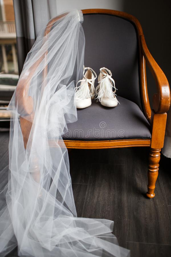 Wedding shoes and veil on the chair. Wedding shoes and veil on a wooden chair stock photos