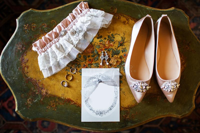 Wedding shoes on the vintage table, bridal garter and rings.  stock image