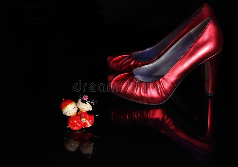 Wedding shoes and a wedding Doll. This graph is a pair of red wedding shoes and a wedding Doll in China style stock photos