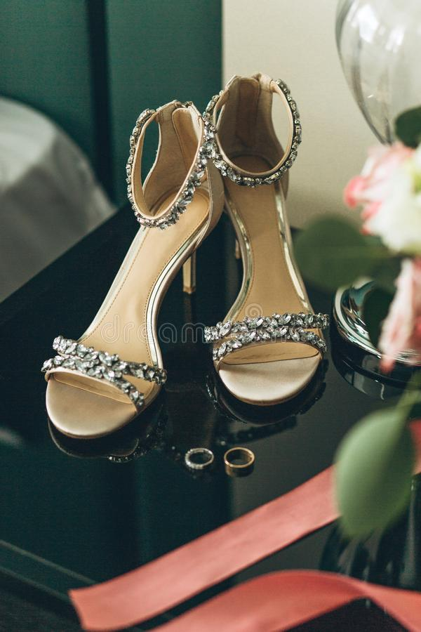 Wedding shoes and wedding rings. Beautiful wedding shoes and a pair of wedding rings nearby. Preparing for the wedding royalty free stock photo