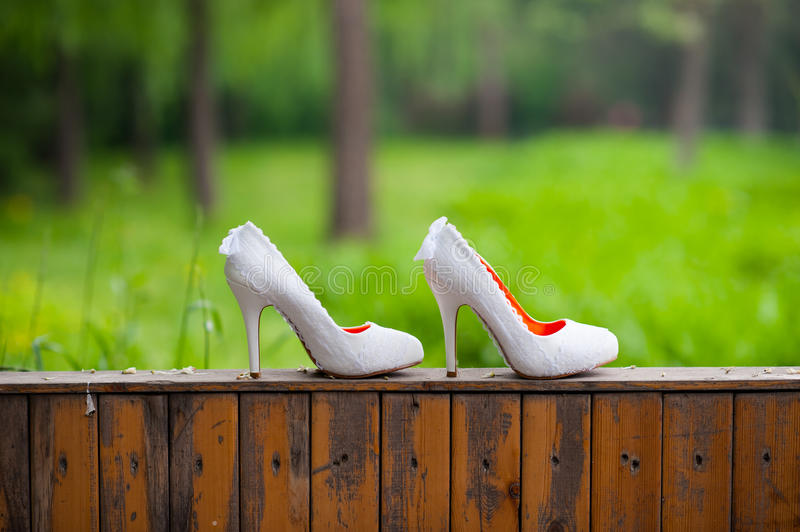 Wedding shoes. Wedding on a wooden fence on a background of green grass shoes stock image