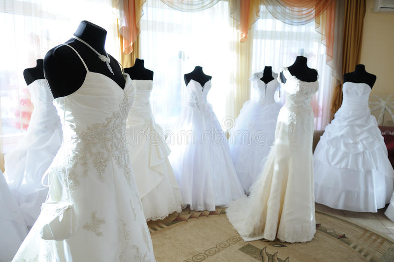 In the wedding showroom. Wedding dresses on dummies in the sunlit showroom royalty free stock photography