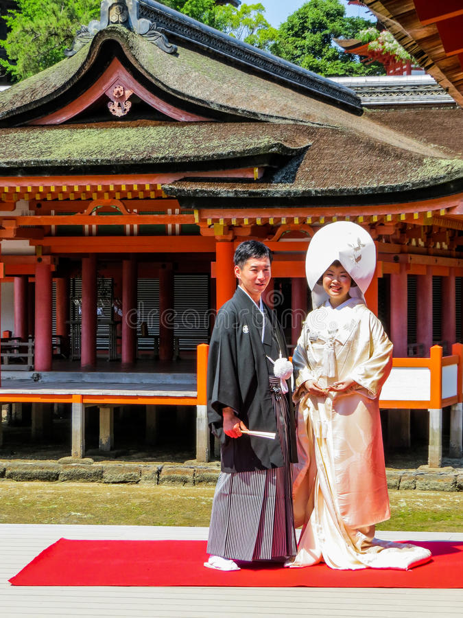 Wedding in the Shrine. Japanese spouses looking happy and tense at the same time, posing for photographers on their wedding day in in Itsukushima Shinto Shrine