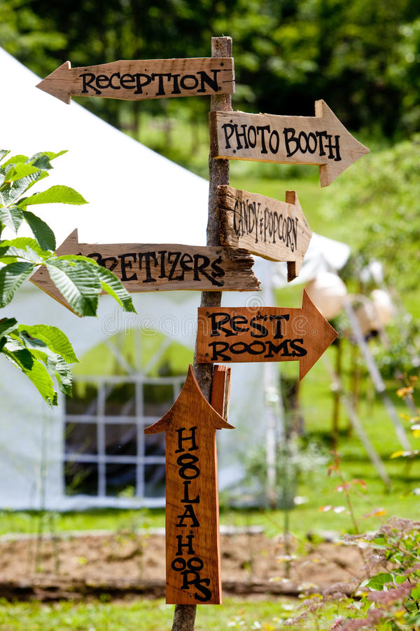 Wedding sign. A very cool and unique wedding sign showing guests directions to various areas and a tent in the background royalty free stock images
