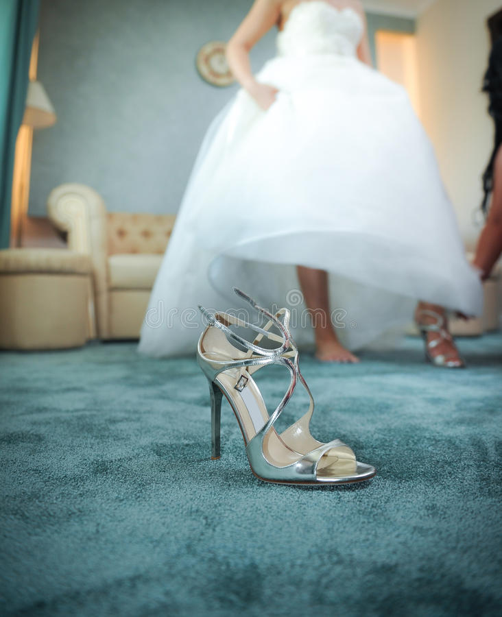 Wedding silver shoe closeup with a bride in background. High heels bridal shoe on carpet. Bride getting ready for special day royalty free stock photo