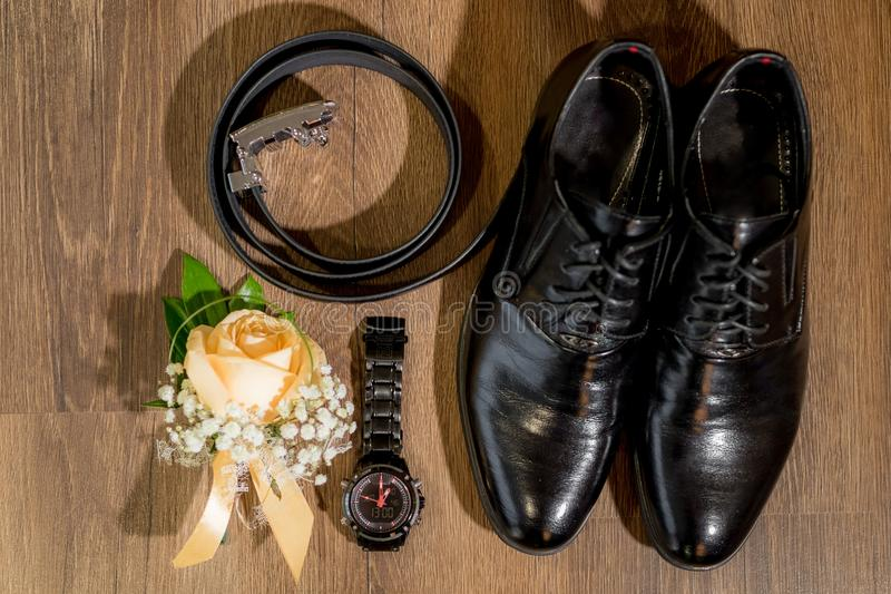 Wedding small things groom shoes watches boutonniere. Groom`s morning. Wedding accessories. Shoes and wedding bouquet, rings, boutonniere and a belt stock photos